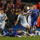 Steaua Bucharest's Alexandru Chipciu, right, is tackled by Chelsea's Ashley Cole, below, during their Champions League group E soccer match at Stamford Bridge, London, Wednesday, Dec. 11, 2013