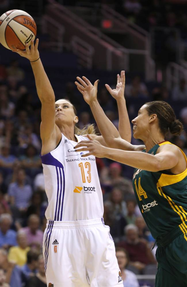 Phoenix Mercury's Penny Taylor (13), of Australia, beats Seattle Storm's Nicole Powell (14) to the ball for a rebound during the second half of a WNBA basketball game on Tuesday, June 3, 2014, in Phoenix.  The Mercury defeated the Storm 87-72
