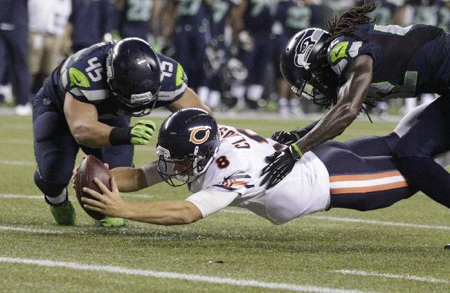 Chicago Bears quarterback Jimmy Clausen (8) falls just short of the goal line as he comes down between Seattle Seahawks' Brock Coyle (45) and Terrance Parks in the second half of an preseason NFL football game, Friday, Aug. 22, 2014, in Seattle