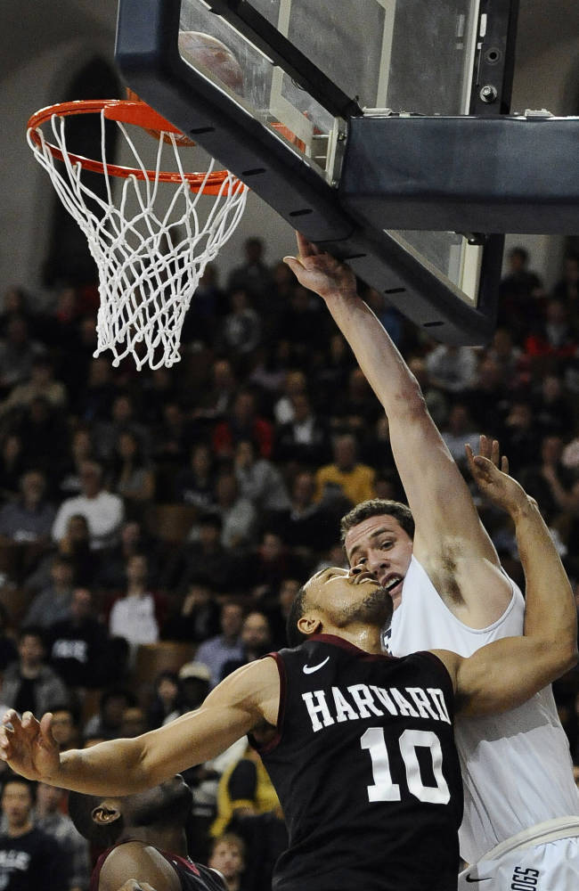 Harvard's Brandyn Curry, left, goes up for a basket as Yale's Jesse Pritchard, right, defends during the second half of an NCAA college basketball game, Friday, March 7, 2014, in New Haven, Conn