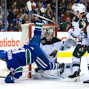 Vancouver Canucks' Brad Richardson, left, is tripped up by Minnesota Wild's Jonas Brodin, back right, of Sweden, in front of Wild goalie Darcy Kuemper as Wild's Kyle Brodziak, right, watches during the first period of an NHL hockey game Friday, Feb. 28, 2