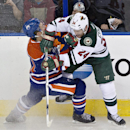 Minnesota Wild's Matt Cooke (24) checks Edmonton Oilers' Andrew Ference (21) during second period NHL hockey action in Edmonton, Canada, Thursday, Feb. 27, 2014 The Associated Press