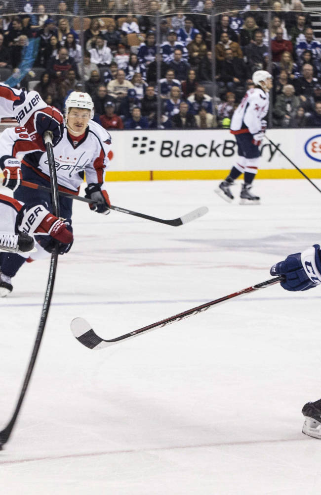 Washington Capitals right winger Eric Fehr, left, gets a shot away under pressure from Toronto Maple Leafs defenseman Morgan Rielly during first period NHL hockey action in Toronto, on Saturday, Nov. 23 , 2013