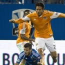 Montreal Impact's Felipe Martins is knocked down by Houston Dynamo's Brian Ching during second-half MLS soccer game action on Wednesday, June 19, 2013, in Montreal. The Impact won 2-0. (AP Photo/The Canadian Press, Paul Chiasson)