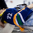 Vancouver Canucks' Daniel Sedin, of Sweden, is taken off the ice on a stretcher after being checked into the boards by Calgary Flames' Paul Byron during second period NHL hockey action in Vancouver, British Columbia, on Sunday April 13, 2014 The Associat