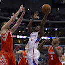 Los Angeles Clippers guard Darren Collison, second from right, puts up a shot as Houston Rockets forward Donatas Motiejunas, left, of Poland, guard Jeremy Lin, second from left, and forward Jordan Hamilton defend during the first half of an NBA basketball