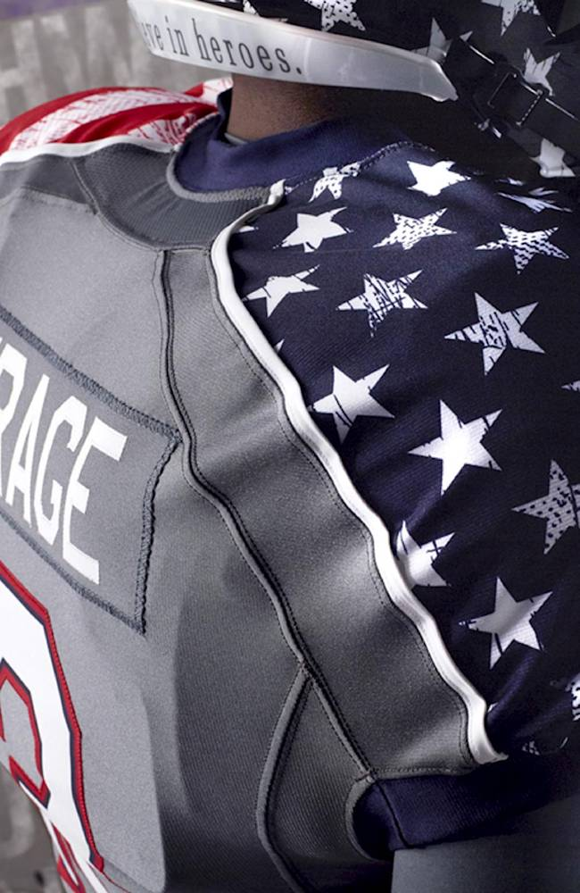 This undated photo provided by Northwestern Athletic Department on Thursday, Nov. 14, 2013, shows a model dressed in the NCAA college football team's new the patriotic-themed uniform. When Northwestern takes the field against Michigan on Saturday, the Wildcats will trade their familiar purple for a set of patriotic uniforms like no other; stars and stripes across the shoulders and a distressed pattern that to some looks like blood stains on a flag. They're simply the latest push by companies that supply athletic equipment to schools to honor the military, and the players love it , especially when they help raise money for soldiers injured in the line of duty