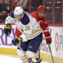 Buffalo Sabres' Matt Moulson (26) and Carolina Hurricanes' Ryan Murphy (7) chase the puck during the first period of a preseason NHL hockey game in Raleigh, N.C., Friday, Oct. 3, 2014 The Associated Press