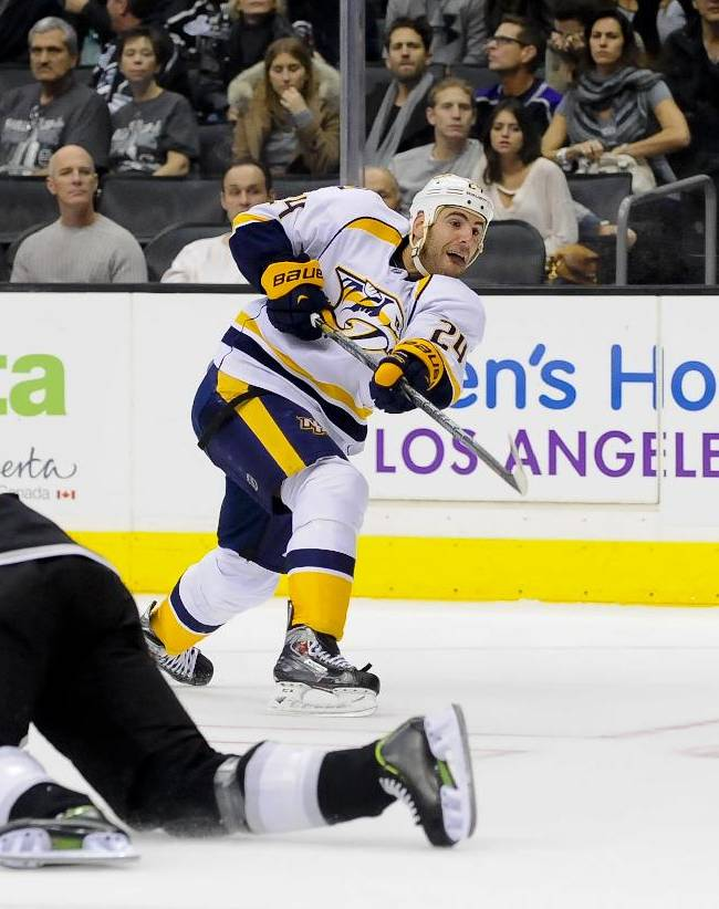 Nashville Predators left wing Eric Nystrom (24) takes a shot after Los Angeles Kings defenseman Robyn Regehr (44), of Brazil, falls leaving an opening during the first period of their NHL hockey game, Saturday, Nov. 2, 2013, in Los Angeles