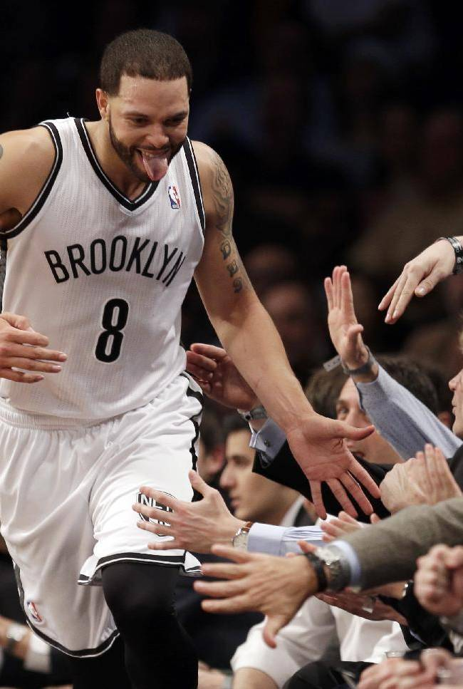 Brooklyn Nets' Deron Williams celebrates with fans after being fouled while scoring during the second half of an NBA basketball game against the Chicago Bulls at the Barclays Center, Monday, March 3, 2014, in New York. The Nets won 96-80