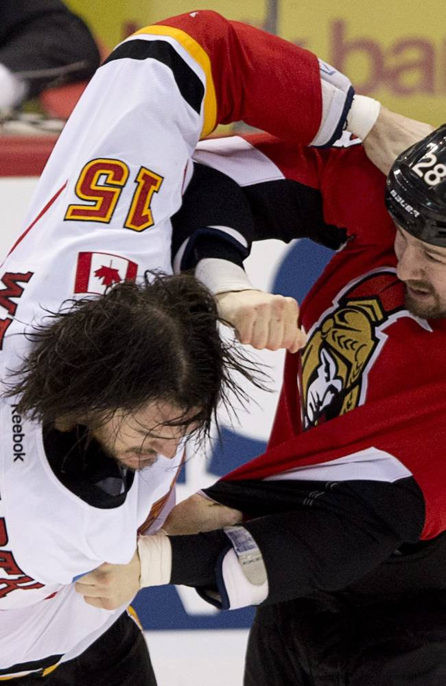 Ottawa Senators Matt Kassian, right, fights with Calgary Flames Kevin Westgarth during second period NHL action Sunday March 30, 2014 in Ottawa, Ontario