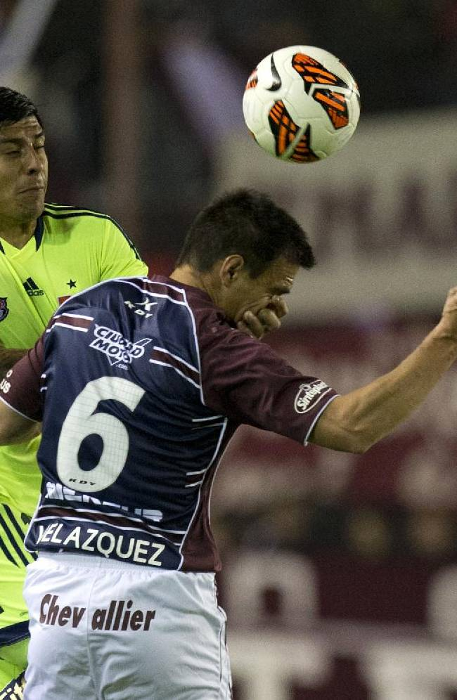 Felipe Gallegos, left, of Chile's Universidad de Chile, vies for the ball with Maximiliano Velazquez of Argentina's Lanus during a Copa Sudamericana soccer match Wednesday, Sept. 18, 2013, in Buenos Aires, Argentina