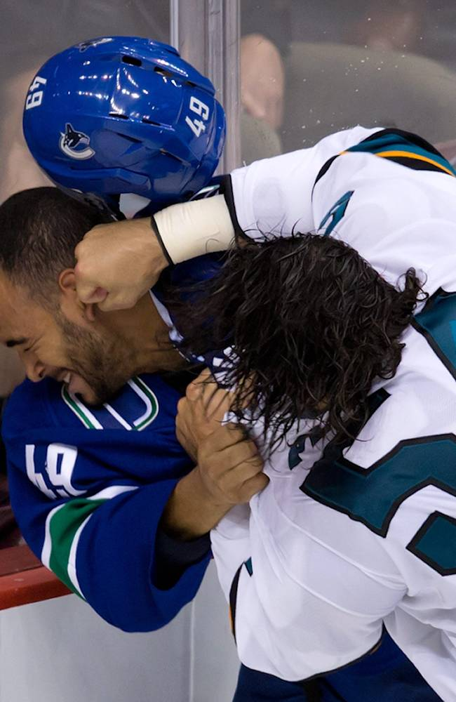 Vancouver Canucks' Darren Archibald, left, and San Jose Sharks' Nick Petrecki fight during the third period of a pre-season NHL hockey game in Vancouver,Columbia on Monday Sept. 16, 2013