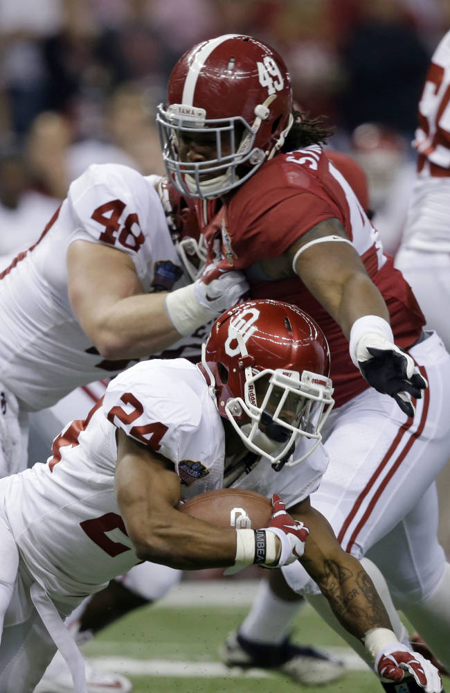 Oklahoma running back Brennan Clay (24) carries as Alabama defensive lineman Ed Stinson (49) tries to tackle during the first half of the Sugar Bowl NCAA college football game, Thursday, Jan. 2, 2014, in New Orleans