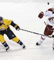 Phoenix Coyotes center Lauri Korpikoski (28), of Finland, and Nashville Predators defenseman Ryan Ellis (4) chase after the puck in the first period of an NHL hockey game on Thursday, April 10, 2014, in Nashville, Tenn. (AP Photo/Mark Humphrey)
