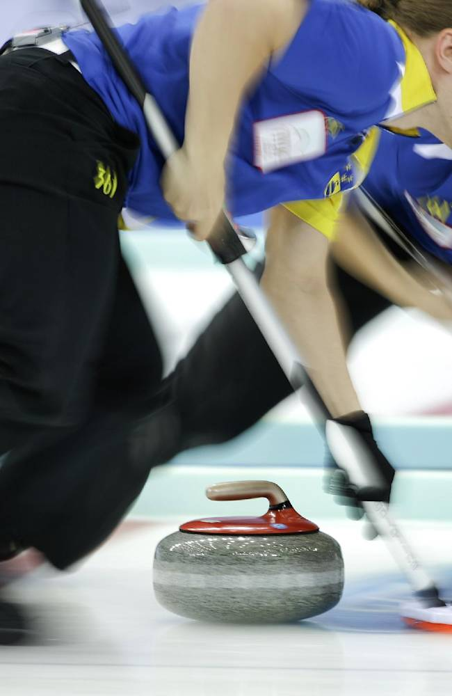 Sweden's Markus Eriksson, left, and Christoffer Sundgren, right, sweep the stone's path during their semi-final match against Canada at the 2014 World Men's Curling Championship held at the Capital Gymnasium in Beijing, China, Saturday, April 5, 2014