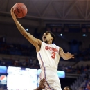 Florida guard Mike Rosario (3) elevates to the basket against Marquette guard Junior Cadougan (5) and forward Jamil Wilson (0) during an NCAA college basketball game in Gainesville, Fla., Thursday, Nov. 29, 2012. (AP Photo/Phil Sandlin)