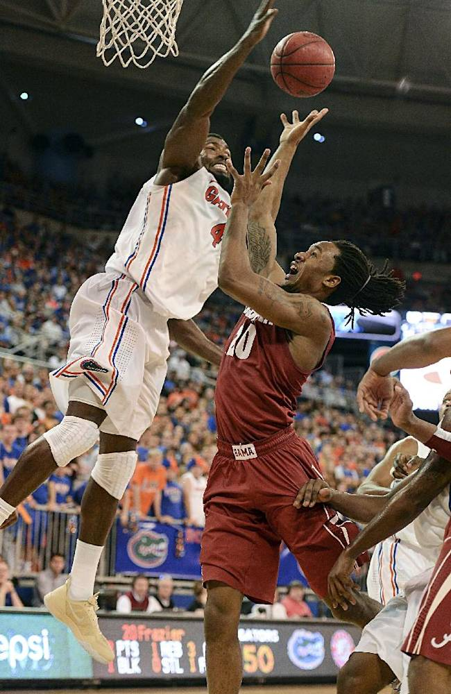 Florida center Patric Young (4) goes high to block a shot by Alabama guard Levi Randolph (20) during the second half of an NCAA college basketball game Saturday, Feb. 8, 2014 in Gainesville, Fla. Florida won the game 78-69