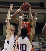 Sam Houston State's James Thomas (20) shoots over Stephen F. Austin's Trey Pinkney (10) and Tanner Clayton (30) during the first half of an NCAA college basketball game in the championship of the Southland Conference tournament Saturday, March 15, 2014, in Katy, Texas. (AP Photo/Bob Levey)