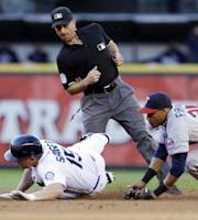 Umpire Quinn Wolcott leans in to watch the play as Seattle Mariners' Kyle Seager safely slides into second base for a double as Minnesota Twins shortstop Pedro Florimon comes in from the right in the second inning of a baseball game Thursday, July 25, 2013, in Seattle. (AP Photo/Elaine Thompson)