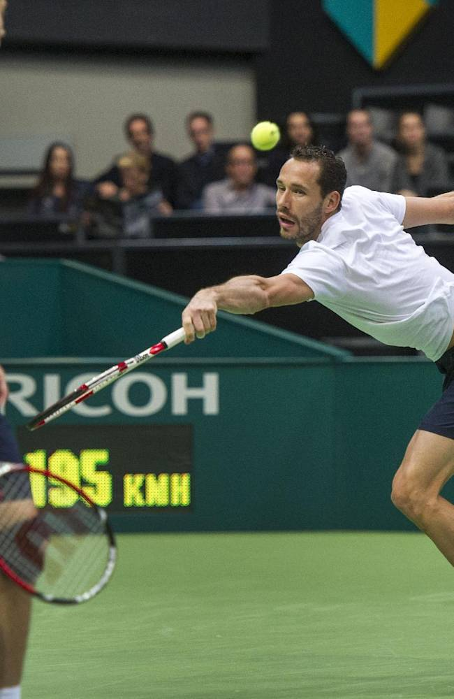 French player Michael Llodra, right,   partnered with Nicolas Mahut, of France,  foreground, returns the ball to Romanian Horia Tecau and Jean-Julien Rojer of The Netherlands, during the men's doubles final, of the 41st ABN AMRO world tennis tournament, at Ahoy Arena,  in Rotterdam, Netherlands, Sunday Feb. 16, 2014