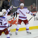 New York Rangers' Kevin Klein, left, celebrates his game-winning goal in overtime with Ryan McDonagh (27) and Derick Brassard during an NHL hockey game against the New Jersey Devils Tuesday, Oct. 21, 2014, in Newark, N.J. The Rangers won 4-3 The Associate