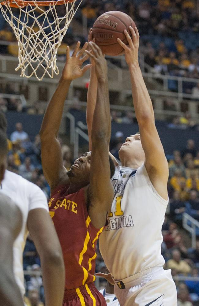 West Virginia's Nathan Adrian, right, rebounds over Iowa State's Melvin Ejim during the first half of an NCAA college basketball game Monday, Feb. 10, 2014, in Morgantown, W.Va