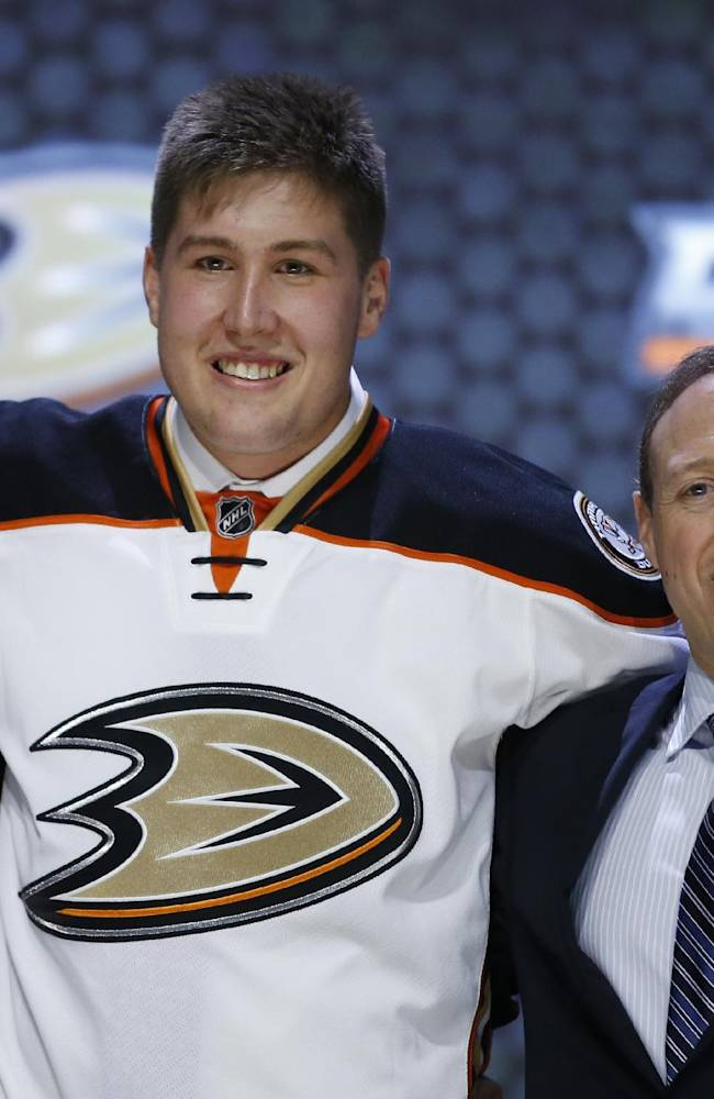 Nicholas Ritchie stands with Anaheim Ducks officials after being chosen 10th overall during the first round of the NHL hockey draft, Friday, June 27, 2014, in Philadelphia