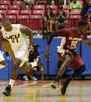 Florida State forward Okaro White, right, looses the ball while driving to the basket alongside VCU forward Treveon Graham, center, and VCU guard Rob Branderberg at a NCAA college basketball game in San Juan, Puerto Rico, Thursday, Nov. 21, 2013. (AP Photo/Ricardo Arduengo)