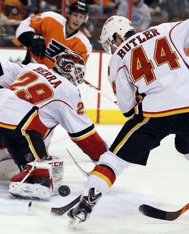 Calgary Flames goalie Reto Barra, left, and Chris Butler, right, try to clear the puck away from the front of the net during the second period of an NHL hockey game against the Philadelphia Flyers, Saturday, Feb. 8, 2014, in Philadelphia. The Flyers won 2-1