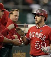 Los Angeles Angels' J.B. Shuck, right, is congratulated by manager Mike Scioscia, left, after Shuck scored against the Oakland Athletics in the first inning of a baseball game, Monday, Sept. 16, 2013, in Oakland, Calif. (AP Photo/Ben Margot)