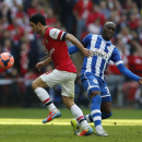 Arsenal's Mikel Arteta, left, competes with Wigan Athletic's Marc-Antoine Fortune during their English FA Cup semifinal soccer match at Wembley Stadium in London, Saturday, April 12, 2014