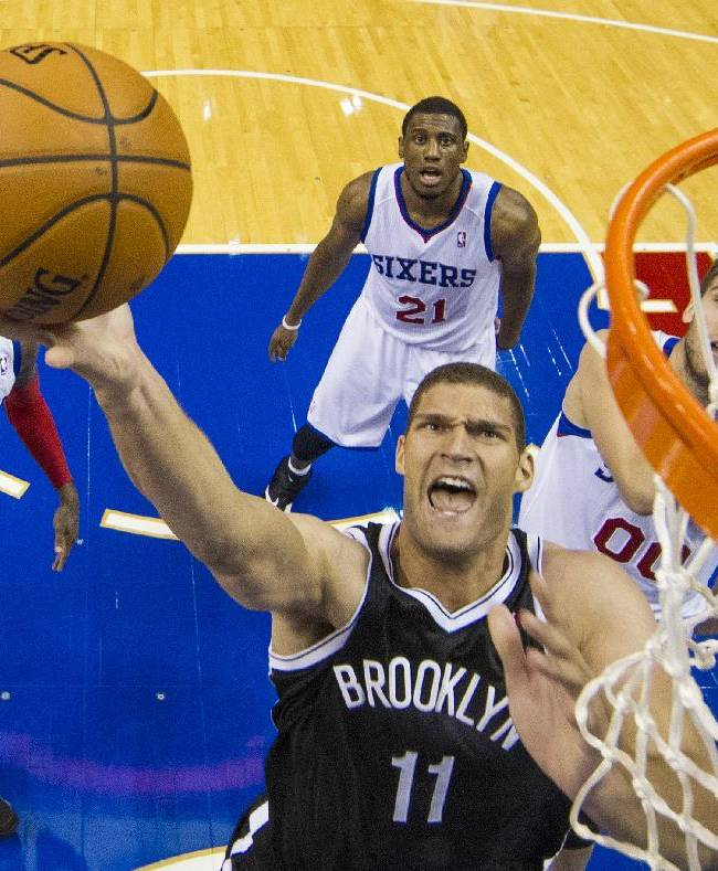 Brooklyn Nets' Brook Lopez goes up for the shot as Philadelphia 76ers' Tony Wroten, left, Thaddeus Young, center, and Spencer Hawes, right, watch during the first quarter of a preseason NBA basketball game, Monday, Oct. 14, 2013, in Philadelphia.  The Nets won 127-97