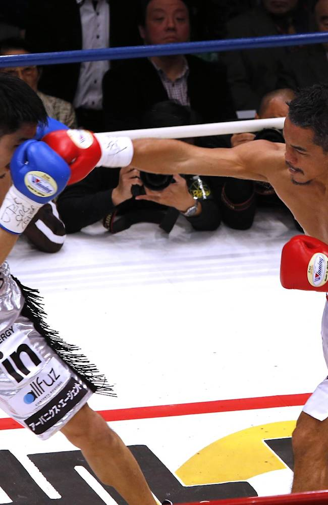 Thailand's Denkaosen Kaovichit, right, sends a right to Japan's Kohei Kono in the first round of their boxing match for the vacant WBA World super flyweight title in Tokyo, Wednesday, March 26, 2014. Kono knocked out Denkaosen in the eighth round to clinch the title
