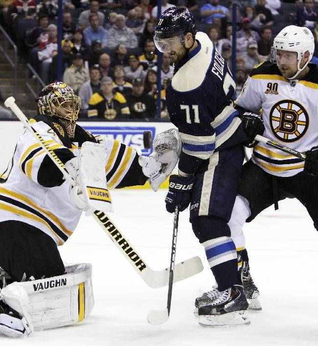 Boston Bruins' Tuukka Rask, left, of Finland, makes a save as teammate Dennis Seidenberg, right, of Germany and Columbus Blue Jackets' Nick Foligno wait for the rebound during the second period of an NHL hockey game Saturday, Oct. 12, 2013, in Columbus, Ohio