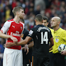Arsenal's Per Mertesacker, left, looks at the referee Roger East after the end of the Englosh Premier League soccer match between Arsenal and Hull City at the Emirates stadium in London Saturday, Oct.18, 2014
