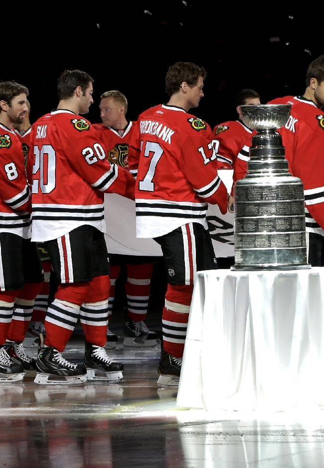 The Chicago Blackhawks carry out the Stanley Cup Championship banner past the Stanley Cup during a ceremony before an NHL hockey game between the Blackhawks and the Washington Capitals Tuesday, Oct. 1, 2013, in Chicago