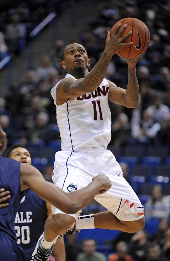 Connecticut's Ryan Boatright (11) drives to the basket as Yale's Javier Duren (20) looks on during the first half of an NCAA college basketball game, in Hartford, Conn., on Monday, Nov. 11, 2013