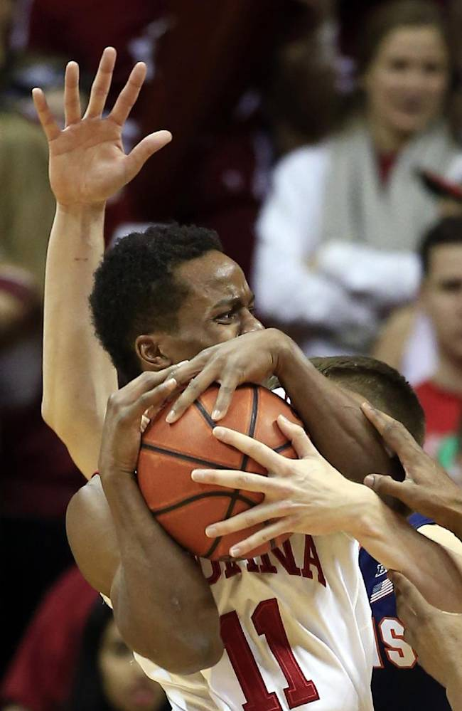 Indiana's Yogi Ferrell (11) is defended by Illinois' Jon Ekey (33) during the first half of an NCAA college basketball game, Sunday, Jan. 26, 2014, in Bloomington, Ind