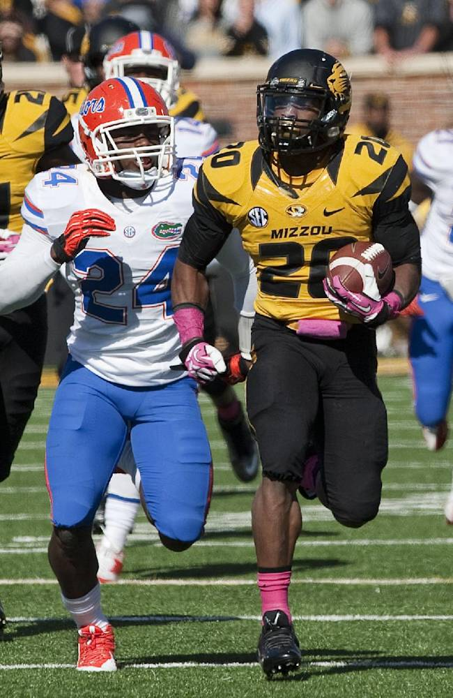 Missouri running back Henry Josey, right runs past Florida's Brian Poole, center, as teammate Bud Sasser, left, runs behind during the fourth quarter of an NCAA college football game Saturday, Oct. 19, 2013, in Columbia, Mo. Josey led all rushers with 137 yards in Missouri's 36-17 victory