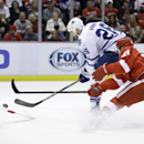 Toronto Maple Leafs right wing Daniel Winnik (26), defended by Detroit Red Wings left wing Tomas Tatar (21) of the Czech Republic, shoots the puck towards goalie Jimmy Howard during the first period of an NHL hockey game in Detroit, Wednesday, Dec. 10, 20