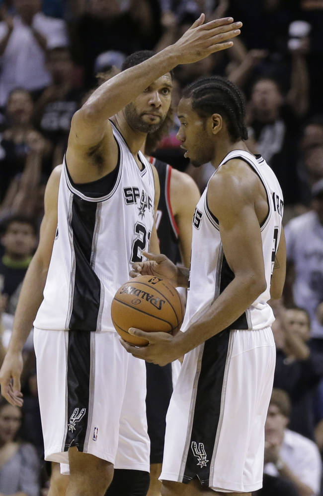 San Antonio Spurs' Tim Duncan (21) celebrates with teammate Kawhi Leonard, right, during the second half of Game 2 of a Western Conference semifinal NBA basketball playoff series against the Portland Trail Blazers, Thursday, May 8, 2014, in San Antonio. San Antonio won 114-97