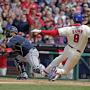 Atlanta Braves' Gerald Laird, left waits for the ball as Philadelphia Phillies' Domonic Brown (9) scores on a single by Ben Revere in the eighth inning of a baseball game Thursday, April 17, 2014, in Philadelphia. The Phillies won 1-0 The Associated Press
