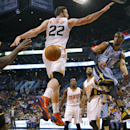 Memphis Grizzlies' Mike Conley (11) dishes off around Phoenix Suns' Miles Plumlee (22) to teammate Zach Randolph during the first half of an NBA basketball game, Monday, April 14, 2014, in Phoenix The Associated Press