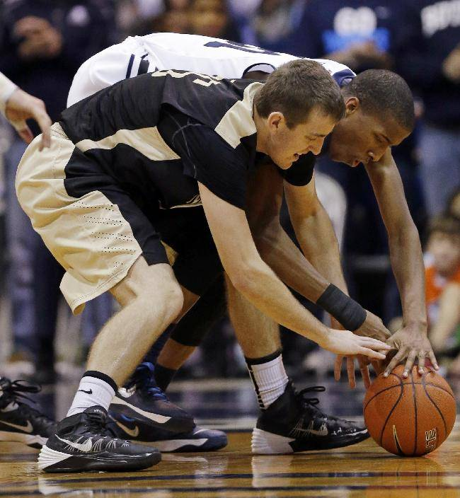 Butler forward Kameron Woods, back and Manchester guard Brady Dolezal go for a loose ball in the second half of an NCAA college basketball game in Indianapolis, Monday, Dec. 9, 2013