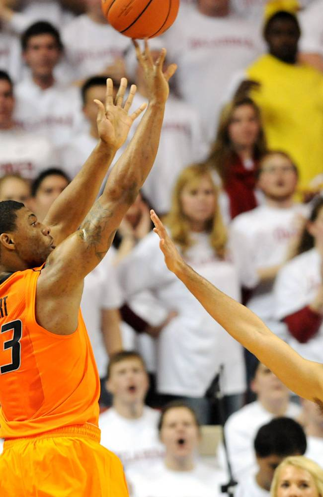 Oklahoma State guard Marcus Smart (33) takes a shot over Oklahoma guard Marcus Smart  (1) during the second half of an NCAA college basketball game in Norman, Okla., Monday, Jan. 27, 2014. Smart scored 22 points in the 76-88 loss to  rival Oklahoma