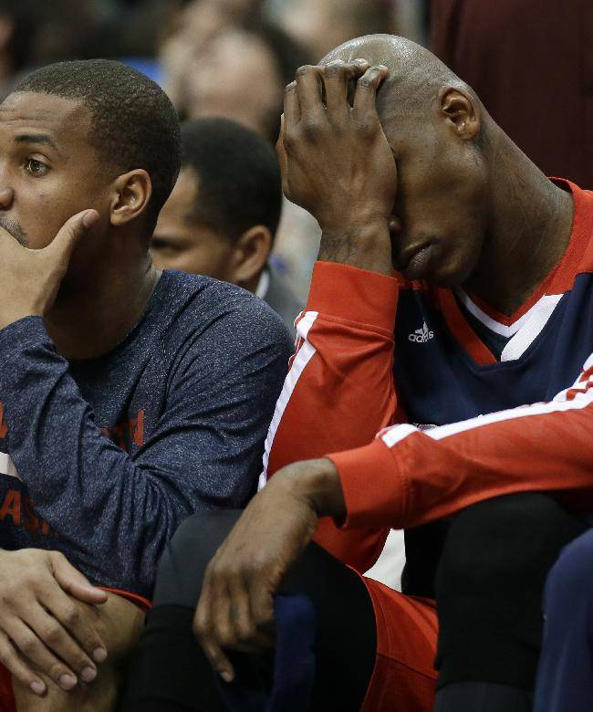 Washington Wizards' Garrett Temple, left, and Al Harrington, right, sit on the bench in the closing minutes of the Wizards' NBA basketball game against the Dallas Mavericks, Tuesday, Nov. 12, 2013, in Dallas. The Mavericks won 105-95