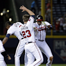 Atlanta Braves' Justin Upton, right, celebrates with teammates B.J. Upton, left, and Chris Johnson after hitting a single to score the winning run in the tenth inning of a baseball game against the Washington Nationals, Friday, April 11, 2014, in Atlanta