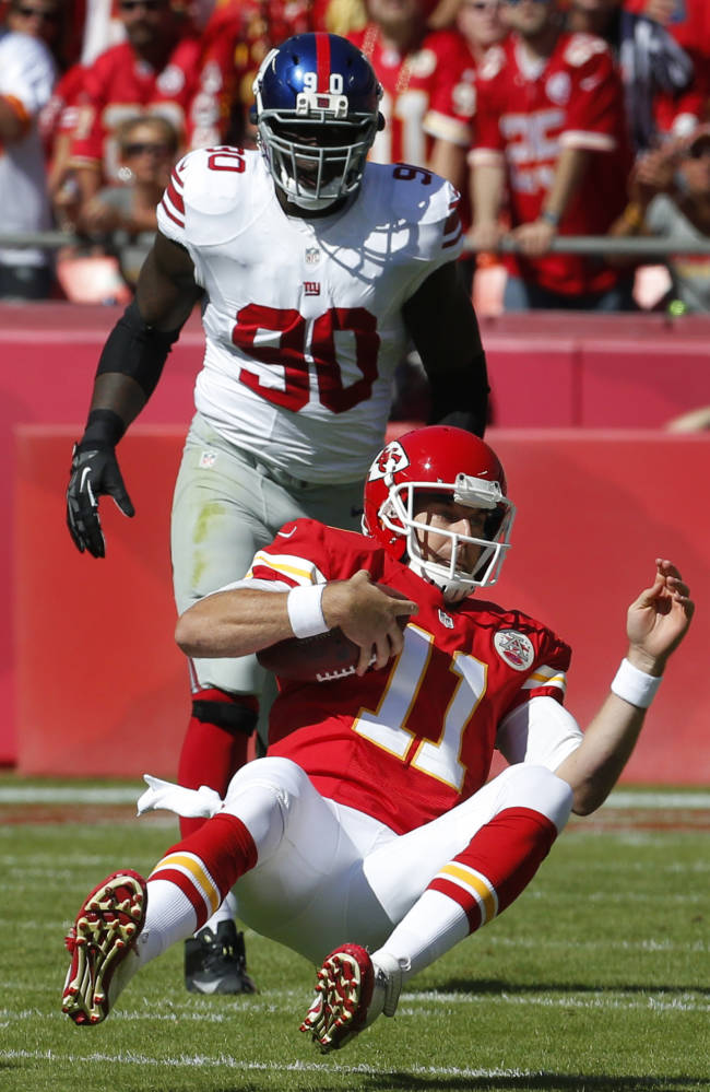 Kansas City Chiefs quarterback Alex Smith (11) slides down after getting past New York Giants defensive end Jason Pierre-Paul (90) during the first half of an NFL football game at Arrowhead Stadium in Kansas City, Mo., Sunday, Sept. 29, 2013