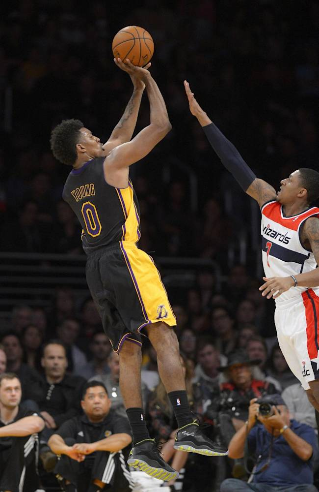 Los Angeles Lakers forward Nick Young, left, puts up a shot as Washington Wizards forward Al Harrington defends during the second half of an NBA basketball game, Friday, March 21, 2014, in Los Angeles. The Wizards won 117-107